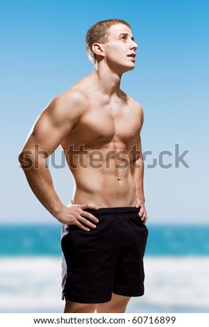 Muscular young male on the beach - stock photo