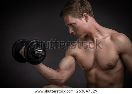 Muscular young man doing exercise with dumbbells on a black background - stock photo