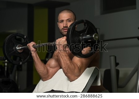 Muscular Young Man Doing Heavy Weight Exercise For Biceps In Gym