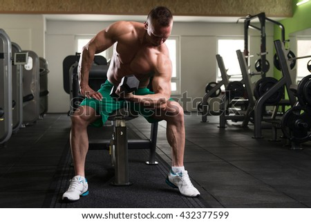 Muscular Young Man Doing Heavy Weight Exercise For Biceps With Dumbbell In Modern Fitness Center Gym - stock photo