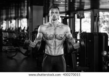 Muscular Young Man Doing Heavy Weight Exercise For Biceps With Dumbbells In Modern Fitness Center Gym - stock photo
