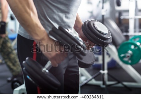Muscular Young Man Doing Heavy Weight Exercise For Biceps With Dumbbells In Modern Fitness Center - stock photo