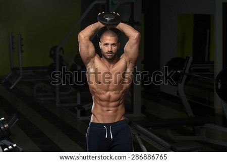 Muscular Young Man Doing Heavy Weight Exercise For Triceps In Gym - stock photo
