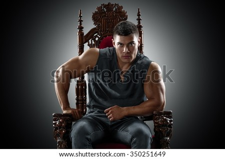 Muscular young man in a T-shirt and jeans, sitting on the throne.  - stock photo