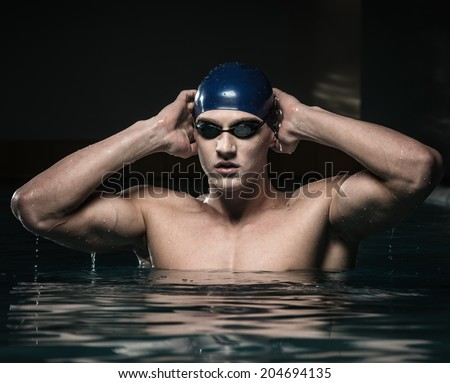 Muscular young man in blue cap in swimming pool - stock photo