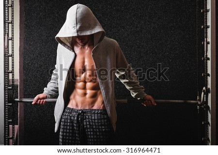 Muscular young man in gray hoodie in gym posing. Fit slim guy in gray sportswear posing against dark gray background. Medium retouch, no filter, horizontal, copy space. - stock photo