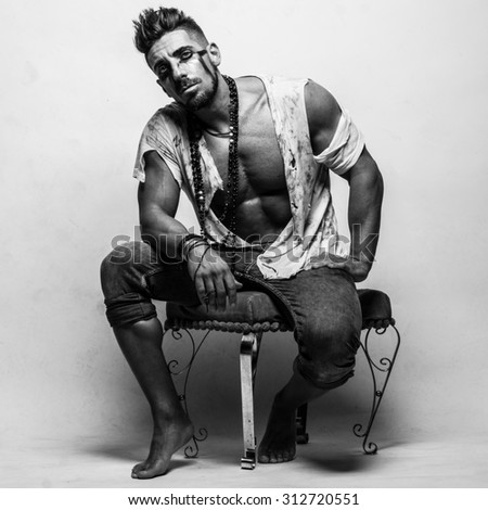 Muscular Young Man in Ragged Clothes Sitting on a Chair and Looking at the Camera in Monochrome Color Capture. - stock photo