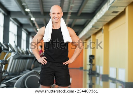 Muscular young man in sports outfit  smiling on gym