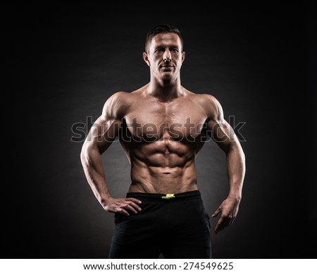 Muscular young man in studio on dark background shows the different movements and body parts - stock photo