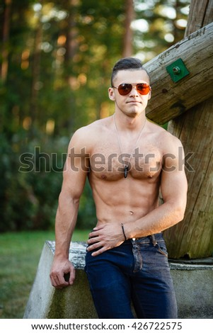 Muscular young man in sunglasses near a log.