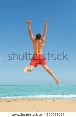 muscular young man jumping on the beach - stock photo