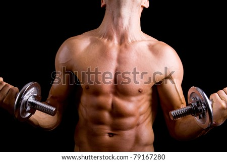 Muscular young man lifting dumbbells on black background.