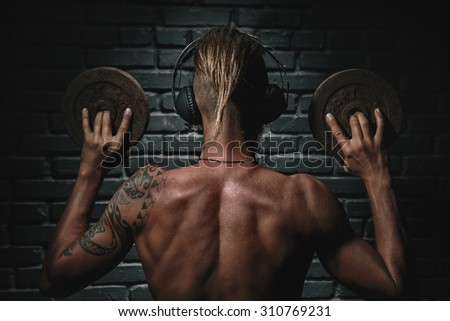 Muscular young man lifting weights and listening to music in headphones - stock photo