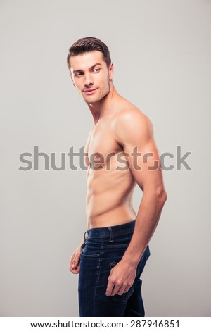 Muscular young man looking away over gray background - stock photo