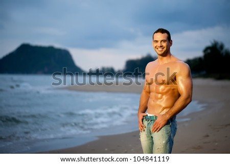 Muscular young man on beach - stock photo