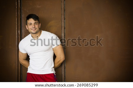 Muscular young man portrait indoors smiling at camera, wearing white t-shirt - stock photo