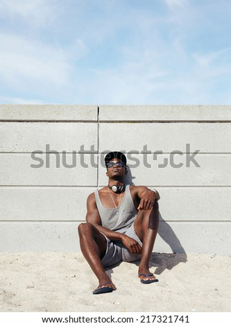 Muscular young man relaxing on the beach. African man leaning to a wall sitting. - stock photo