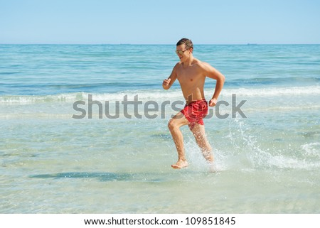 muscular young man running along the coast - stock photo