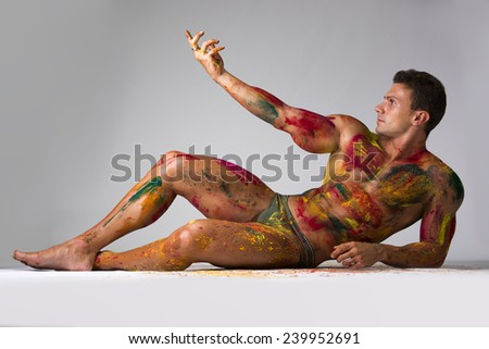 Muscular young man shirtless with skin painted with Holi colors, laying down on the floor striking a pose - stock photo