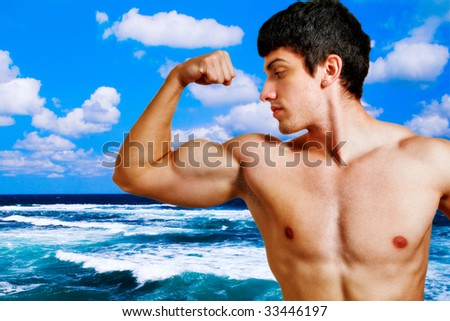 Muscular young man showing his biceps on the beach - stock photo