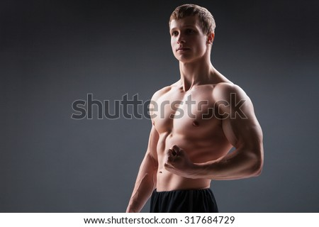 Muscular young man  shows the different movements and body parts - stock photo