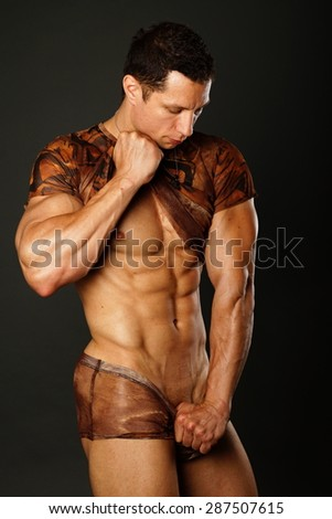 Muscular young man standing poses on the dark background