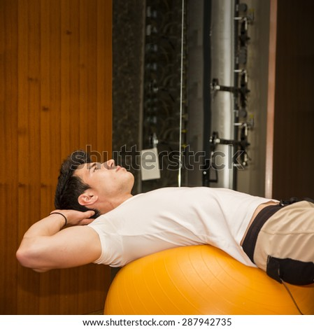 Muscular young man training, exercising abs on fitness ball