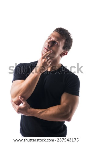 Muscular young man unsure or confused, holding chin with hand, looking up, isolated - stock photo