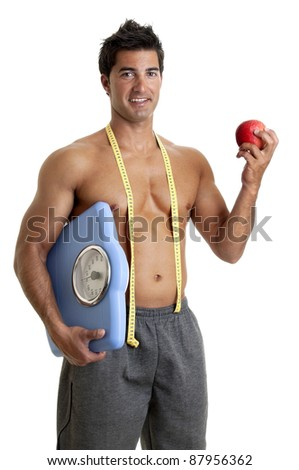 Muscular young man with apple and weight scale