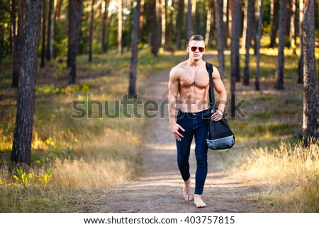 Muscular young man with bag in a forest. - stock photo