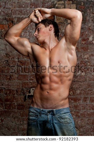 Muscular young naked sexy boy posing in jeans on the background of a brick wall with their hands behind their head - stock photo