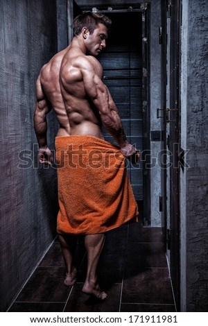 Muscular young sexy bodybuilder wrapped in a towel goes in shower
