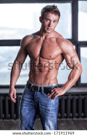 Muscular young sexy guy posing in studio in jeans and bare-chested - stock photo