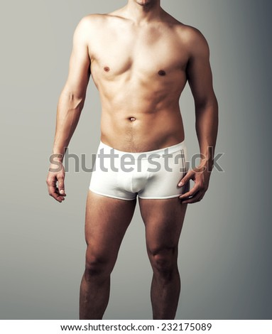 Muscular young sexy handsome man posing in white pants. Male underwear model on gray background
