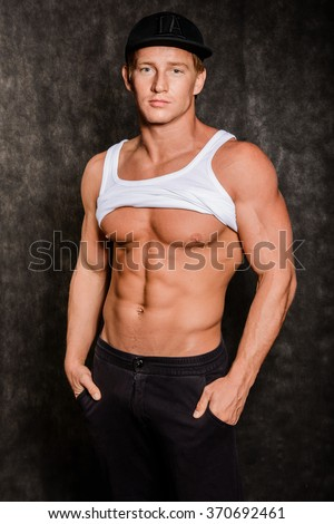 Muscular young sexy man  in a vest and a cap with a naked torso on black background - stock photo