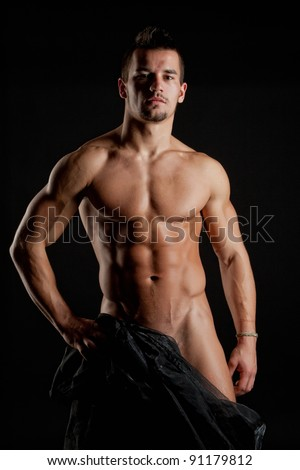Muscular young sexy naked cute man wrapped in black silk - stock photo