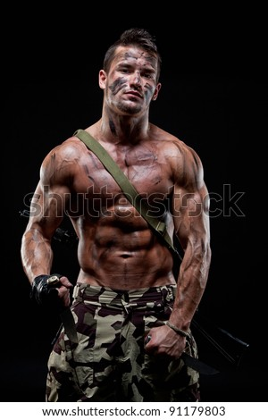 Muscular young sexy naked dirty soldiers with knives and weapons behind  and in camouflage paint - stock photo