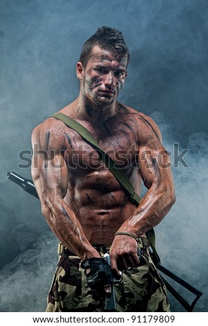 Muscular young sexy naked dirty soldiers with weapons in army clothes in the smoke - stock photo