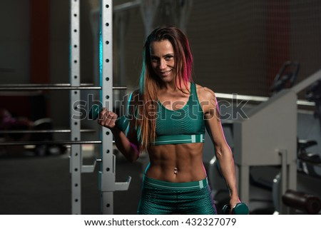 Muscular Young Woman Doing Heavy Weight Exercise For Biceps With Dumbbells In A Fitness Center Gym - stock photo