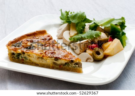 Mushroom and spinach quiche served with a garden salad - stock photo