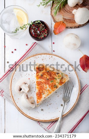 Mushroom, champignon pie, quiche slice on a ceramic plate on a white wooden background - stock photo