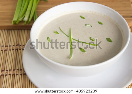 Mushroom cream soup and chives on a table, food - stock photo