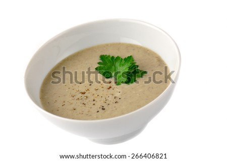 Mushroom cream soup in white bowl garnished with grated pepper and parsley leaf. Isolated - stock photo