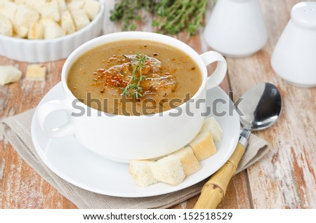 Mushroom cream soup with croutons and thyme in a white bowl horizontal