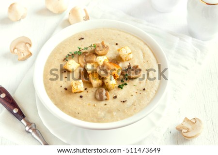 Mushroom cream soup with croutons, herbs and spices over white wooden background with copy space