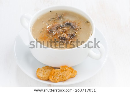 mushroom cream soup with croutons on white wooden table, close-up - stock photo