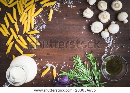 Mushroom pasta ingredients: penne, mushrooms, a jug of cream, pesto sauce, fresh herbs and spices on a dark wood background with a copy space in the center - stock photo