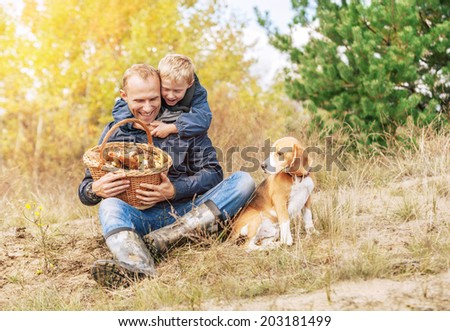 Mushroom picking. Father and little son happy with their catch - stock photo