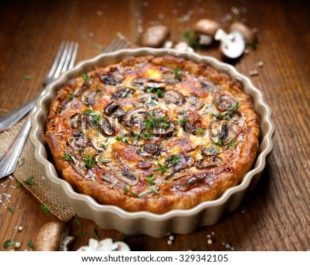 Mushroom quiche on a wooden rustic table - stock photo