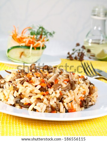 Mushroom risotto served with vegetables salad. - stock photo